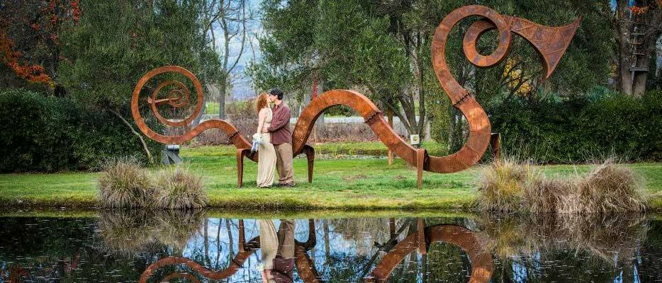 Bride and groom in front of EcoTerra's serpent sculpture